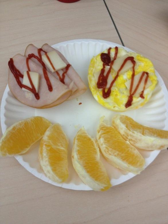 Protein roll, eggs, chicken breast slices and 1/2 orange
