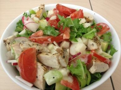 Yummy salad, with tomato, tomattilo, jicama, avocado, onion, fresee greens, radishes and chicken breast